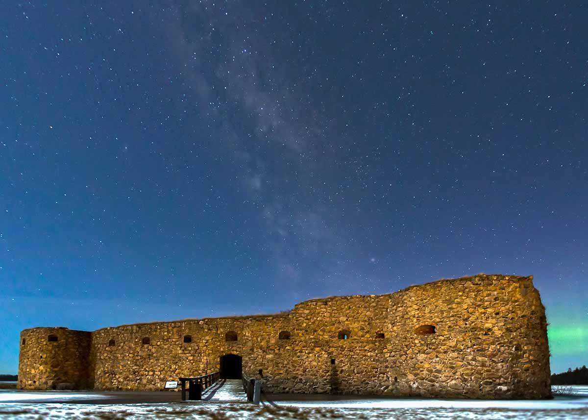 Kronoberg slottsruin utanför Växjö. Stjärnhimmel med Vintergatan synlig och norrsken i bakgrunden.
